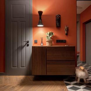 Пример оригинального дизайна: большой коридор в современном стиле с оранжевыми стенами, паркетным полом среднего тона и коричневым полом