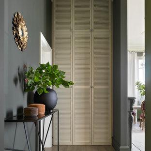 Стильный дизайн: коридор в стиле современная классика с черными стенами, светлым паркетным полом и бежевым полом - последний тренд