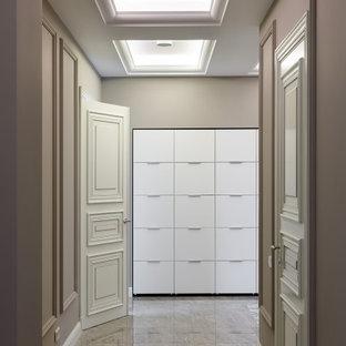 Стильный дизайн: коридор в современном стиле с бежевыми стенами, бежевым полом и правильным освещением - последний тренд