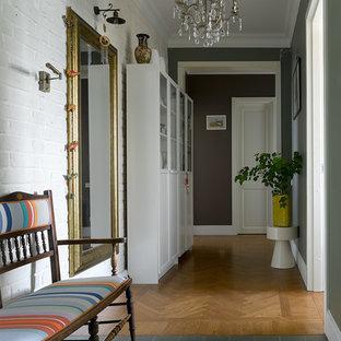 Eklektisk inredning av en hall, med vita väggar, mellanmörkt trägolv och brunt golv
