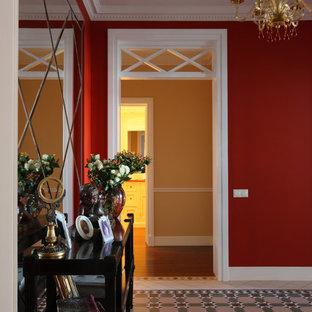 Exempel på en mellanstor klassisk hall, med röda väggar och klinkergolv i keramik
