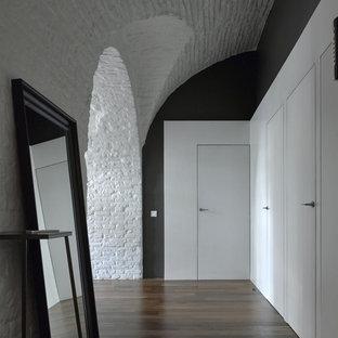 モスクワのコンテンポラリースタイルのおしゃれな廊下 (黒い壁、濃色無垢フローリング、茶色い床) の写真