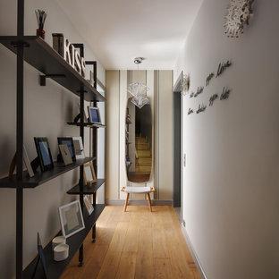 На фото: коридор в современном стиле с белыми стенами и паркетным полом среднего тона с