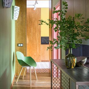 Réalisation d'un couloir bohème avec un mur vert, un sol en bois brun et un sol marron.