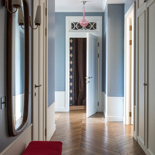 This is an example of a midcentury hallway in Moscow with blue walls, medium hardwood floors and brown floor.