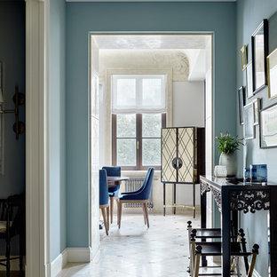 Cette image montre un couloir traditionnel avec un mur bleu, un sol en travertin et un sol beige.