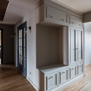 Inspiration för mellanstora moderna hallar, med vita väggar, laminatgolv och brunt golv