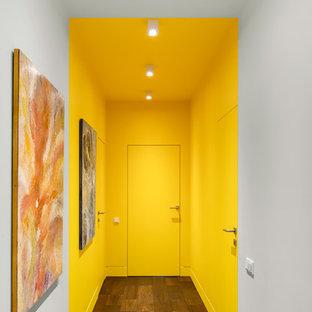 Idee per un ingresso o corridoio minimal con pareti gialle, parquet scuro e pavimento marrone