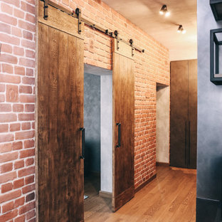 他の地域の中くらいのインダストリアルスタイルのおしゃれな廊下 (茶色い壁、濃色無垢フローリング、茶色い床、表し梁、レンガ壁) の写真