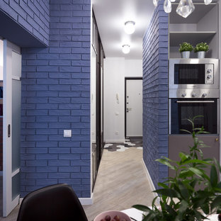 Bild på en liten funkis hall, med blå väggar, vinylgolv och beiget golv
