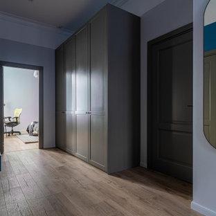 Minimalistisk inredning av en mellanstor hall, med grå väggar, laminatgolv och brunt golv
