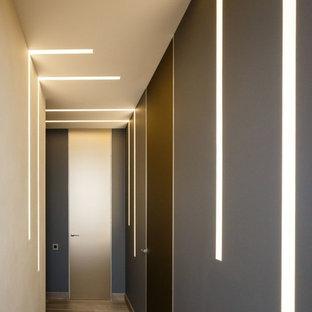 Bild på en funkis hall, med grå väggar, ljust trägolv och beiget golv