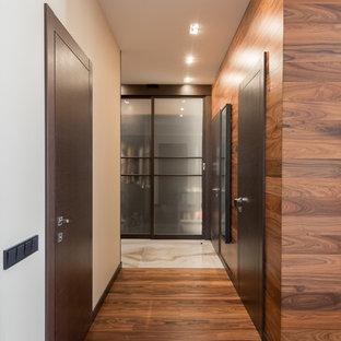 Пример оригинального дизайна интерьера: большой коридор в современном стиле с коричневыми стенами и паркетным полом среднего тона