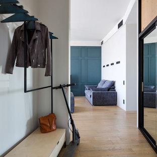 На фото: коридоры в современном стиле с серыми стенами, паркетным полом среднего тона и коричневым полом