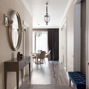 На фото: коридор в стиле неоклассика (современная классика) с бежевыми стенами и серым полом с
