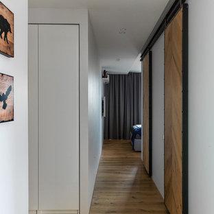 На фото: коридоры в стиле лофт с белыми стенами и паркетным полом среднего тона