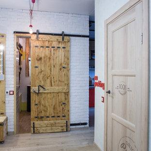 На фото: коридор в стиле лофт с белыми стенами и светлым паркетным полом с