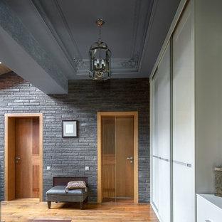 На фото: большой коридор в современном стиле с серыми стенами, темным паркетным полом и коричневым полом с
