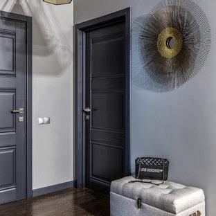 На фото: коридор в современном стиле с серыми стенами, темным паркетным полом и коричневым полом с