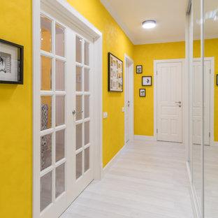Свежая идея для дизайна: коридор в стиле современная классика с желтыми стенами, белым полом и деревянным полом - отличное фото интерьера