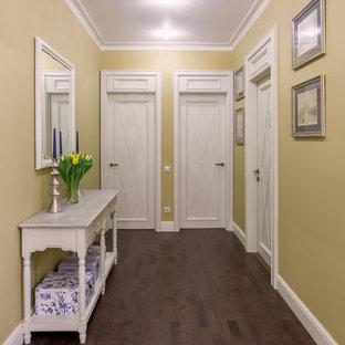 Inspiration för en vintage hall, med gula väggar och mörkt trägolv