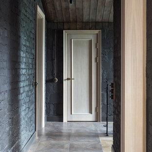 Industriell inredning av en mellanstor hall, med svarta väggar och klinkergolv i porslin