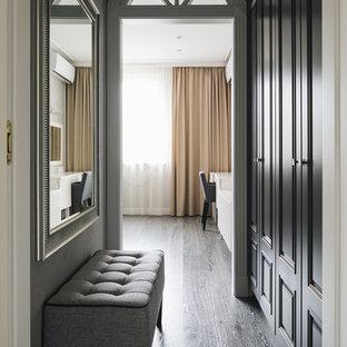 Idée de décoration pour un couloir tradition avec un mur gris, un sol en bois foncé et un sol noir.