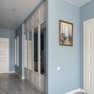 サンクトペテルブルクの中サイズのトランジショナルスタイルのおしゃれな廊下 (青い壁、ラミネートの床、グレーの床) の写真