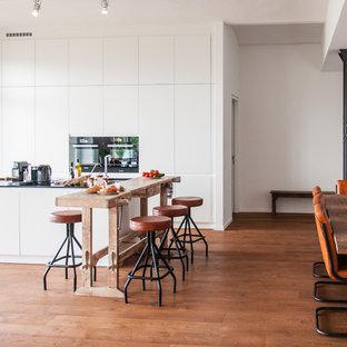 Foto di un'ampia cucina ad ambiente unico stile shabby con ante bianche, top in granito e pavimento in legno massello medio