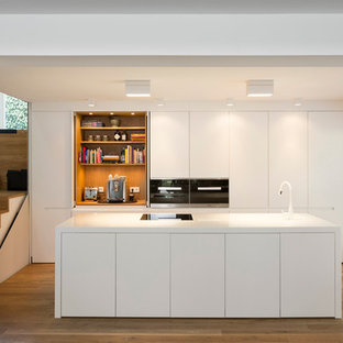 Mid-sized modern open concept kitchen photos - Mid-sized minimalist galley medium tone wood floor and brown floor open concept kitchen photo in Frankfurt with flat-panel cabinets, white cabinets, an island and paneled appliances