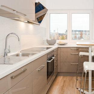 Geschlossene, Kleine Moderne Küche ohne Insel in L-Form mit Einbauwaschbecken, flächenbündigen Schrankfronten, braunen Schränken, Marmor-Arbeitsplatte, Küchenrückwand in Weiß, Rückwand aus Marmor, schwarzen Elektrogeräten, braunem Holzboden und braunem Boden in Berlin