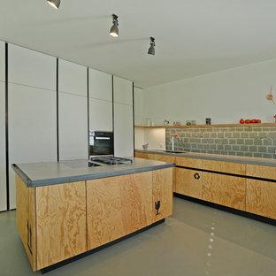 Foto di una grande cucina industriale con lavello integrato, ante lisce, ante in legno scuro, top in superficie solida, paraspruzzi grigio, paraspruzzi con lastra di vetro, elettrodomestici in acciaio inossidabile, pavimento in cemento e isola