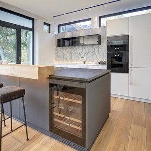 Offene, Zweizeilige, Mittelgroße Moderne Küche mit flächenbündigen Schrankfronten, weißen Schränken, schwarzen Elektrogeräten, hellem Holzboden, beigem Boden, Einbauwaschbecken und Halbinsel in München