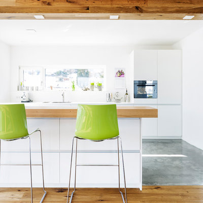 Inspiration for a mid-sized contemporary galley concrete floor and gray floor open concept kitchen remodel in Stuttgart with a single-bowl sink, flat-panel cabinets, white cabinets, stainless steel countertops, white backsplash, glass sheet backsplash, black appliances, a peninsula and white countertops