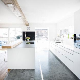 Offene, Zweizeilige, Mittelgroße Moderne Küche mit Waschbecken, flächenbündigen Schrankfronten, weißen Schränken, Edelstahl-Arbeitsplatte, Küchenrückwand in Weiß, Glasrückwand, schwarzen Elektrogeräten, Betonboden, Kücheninsel, grauem Boden und weißer Arbeitsplatte in Stuttgart