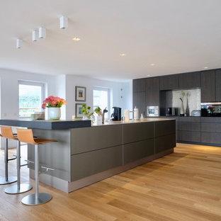 Offene, Einzeilige, Geräumige Moderne Küche mit flächenbündigen Schrankfronten, dunklen Holzschränken, Küchenrückwand in Metallic, schwarzen Elektrogeräten, braunem Holzboden, zwei Kücheninseln und braunem Boden in Köln