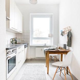 Mittelgroße, Einzeilige Nordische Wohnküche mit Keramikboden, flächenbündigen Schrankfronten, beigen Schränken, Küchenrückwand in Weiß, Küchengeräten aus Edelstahl, grauem Boden und grauer Arbeitsplatte in Berlin