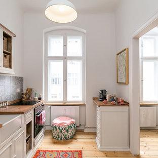 Einzeilige Skandinavische Küche ohne Insel mit Landhausspüle, profilierten Schrankfronten, weißen Schränken, Arbeitsplatte aus Holz, bunter Rückwand, hellem Holzboden und beigem Boden in Berlin