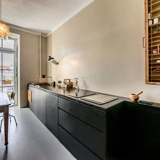 ミュンヘンの小さいインダストリアルスタイルのおしゃれなキッチン (ドロップインシンク、フラットパネル扉のキャビネット、黒いキャビネット、ベージュキッチンパネル、リノリウムの床、アイランドなし) の写真