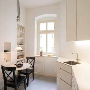 Geschlossene, Einzeilige, Kleine Moderne Küche ohne Insel mit Einbauwaschbecken, flächenbündigen Schrankfronten, weißen Schränken, Küchenrückwand in Weiß, grauem Boden und weißer Arbeitsplatte in Berlin