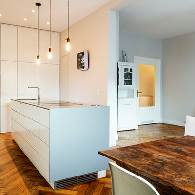 Example of a mid-sized trendy single-wall medium tone wood floor and brown floor open concept kitchen design in Munich with flat-panel cabinets, white cabinets, an island, an integrated sink, solid surface countertops, white backsplash, limestone backsplash and stainless steel appliances