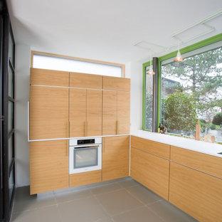 Geschlossene, Mittelgroße Nordische Küche ohne Insel in U-Form mit Waschbecken, Glasfronten, hellen Holzschränken, Mineralwerkstoff-Arbeitsplatte, Keramikboden, grauem Boden und weißer Arbeitsplatte in Sonstige