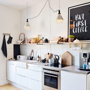Photo of a small scandinavian single-wall eat-in kitchen in Dusseldorf with a farmhouse sink, flat-panel cabinets, white cabinets, stainless steel appliances, light hardwood floors, no island, stainless steel benchtops, white splashback and ceramic splashback.