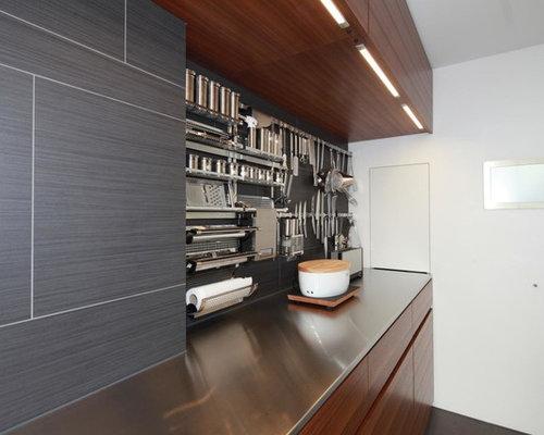 Moderne Küche Mit Flächenbündigen Schrankfronten, Dunklen Holzschränken,  Edelstahl Arbeitsplatte Und Küchenrückwand In Grau