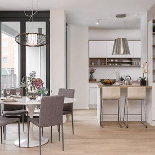 Zweizeilige, Mittelgroße Moderne Wohnküche mit Halbinsel, flächenbündigen Schrankfronten, weißen Schränken, Arbeitsplatte aus Holz, Küchenrückwand in Weiß, hellem Holzboden, beigem Boden und brauner Arbeitsplatte in Berlin