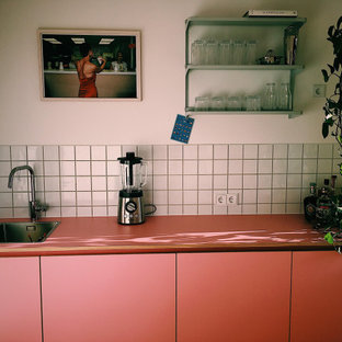 Small contemporary enclosed kitchen photos - Example of a small trendy single-wall enclosed kitchen design in Berlin with white backsplash, no island and pink countertops