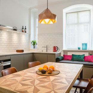ベルリンの中サイズのエクレクティックスタイルのおしゃれなダイニングキッチン (ドロップインシンク、フラットパネル扉のキャビネット、グレーのキャビネット、人工大理石カウンター、白いキッチンパネル、サブウェイタイルのキッチンパネル、パネルと同色の調理設備、無垢フローリング、ベージュの床) の写真