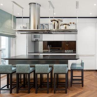 Mittelgroße Moderne Küche in L-Form mit Unterbauwaschbecken, flächenbündigen Schrankfronten, weißen Schränken, Küchenrückwand in Schwarz, Glasrückwand, Elektrogeräten mit Frontblende, Kücheninsel, braunem Boden und schwarzer Arbeitsplatte in Berlin
