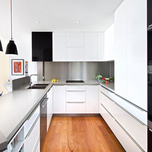 Photo of a contemporary u-shaped kitchen in Brisbane with a double-bowl sink, flat-panel cabinets, white cabinets, metallic splashback, black appliances, medium hardwood floors, a peninsula, brown floor and grey benchtop.