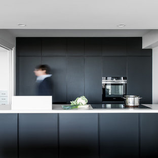 Small modern kitchen in Brisbane with flat-panel cabinets, black cabinets, quartz benchtops, white benchtop and black appliances.